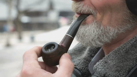 Close-up of smoking man holding a tobacco pipe outdoors