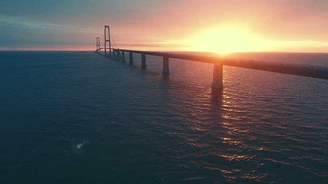 Aerial view of large bridge over the sea at evening. Danish great belt bridge at sunset.