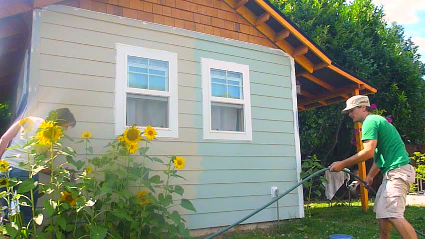 Man and woman couple paint new construction in the summer, time lapse.