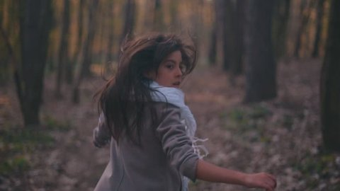 Small teenage girl with long brunette hair and stylish look. Scared little girl running in the forest, she looks around terrified as something is following her. Deserted scary forest, nightmare.
