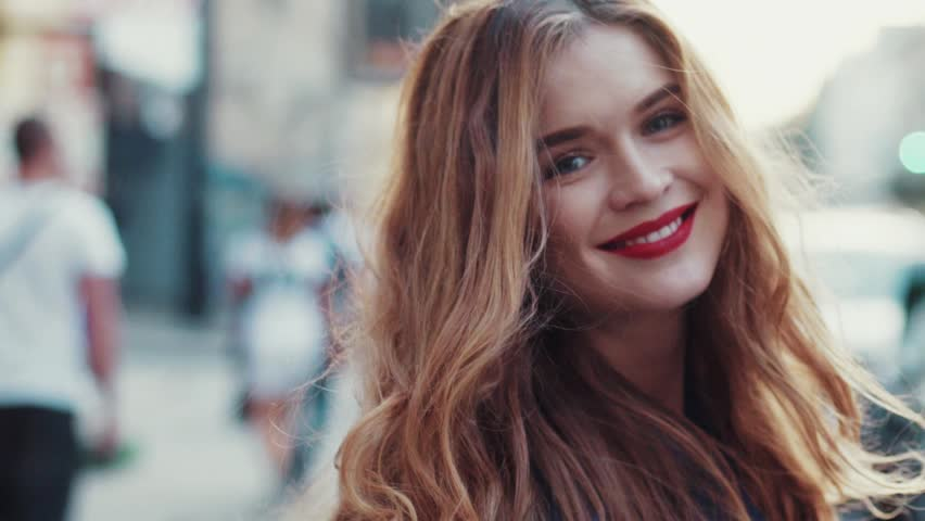 Gorgeous young woman with beautiful blue eyes and golden long hair, with a bright red lipstick. Attractive young lady is walking down the city street, turns to camera and gives a lovely playful smile. | Shutterstock HD Video #23381665