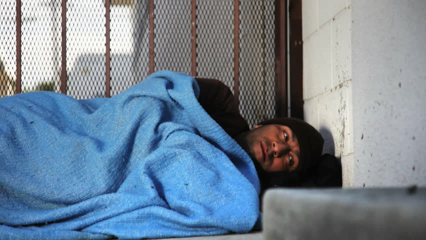 Homeless man trying to sleep on the sidewalk