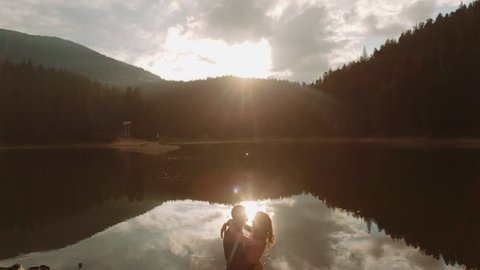 Amazing aerial view of young adorable couple embracing, kissing each other by the deep lake in the green dense mountain region. Summertime, sunset. Couple goals. Forever in love. Love story.