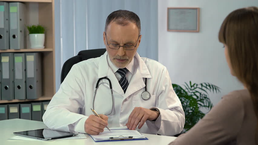 Family doctor talking to patient and filling out medical insurance, health care | Shutterstock HD Video #23400619