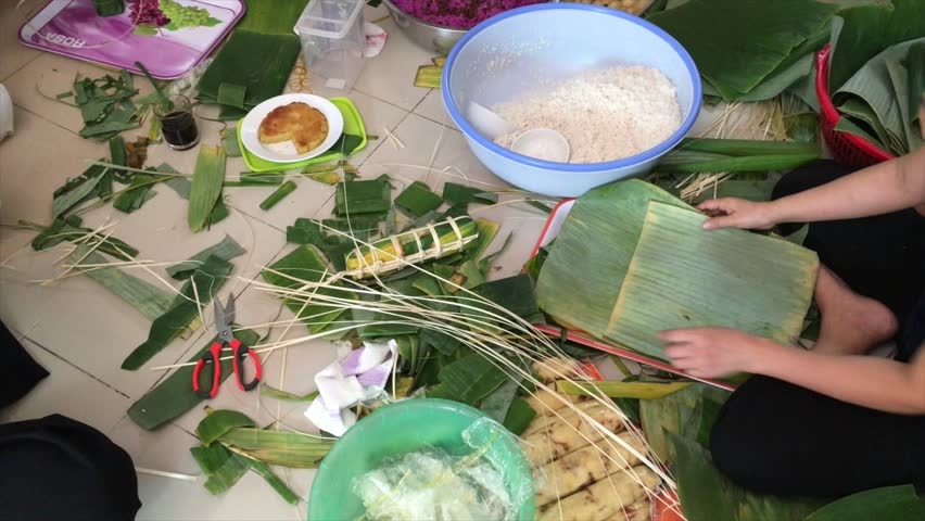 Women form banh tet pies - glutinous rice pies. Banh tet is a must have traditional food on Vietnamese Lunar New Year.