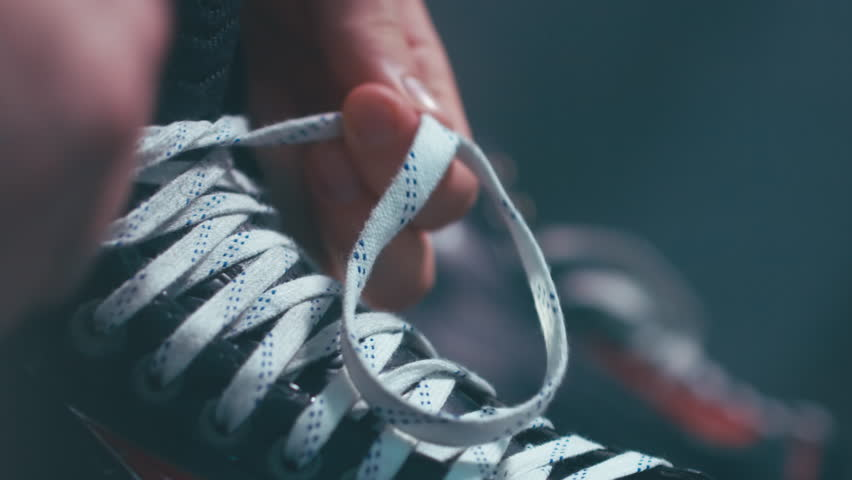 EXTREME CU Caucasian ice hockey player tightening laces on his skates in the locker room, preparing for the game. 4K UHD 60 FPS RAW edited footage
