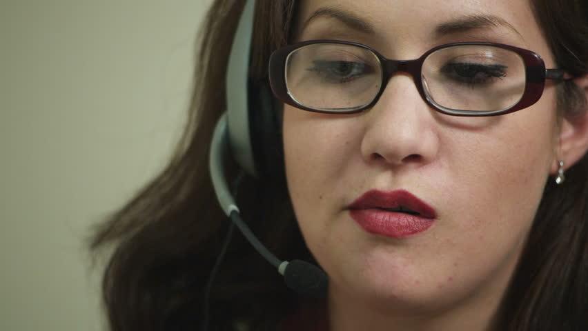 office worker wearing headset chews bubble gum
