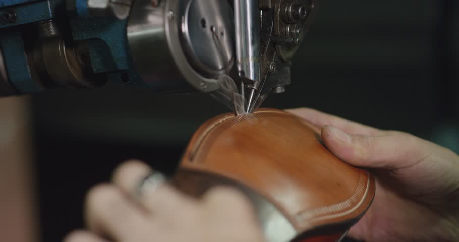 Slow motion close up shot of shoe making by hand.