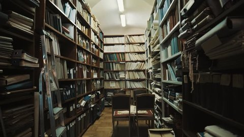 Fluorescent bulbs lights up in an old style library interior. Books and folders