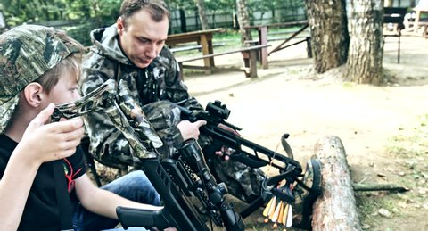 Shooting a crossbow. A man teaches a child to shoot.