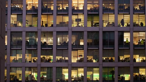 Time-lapse of an office at night panning down to show workers leaving themes of routines working late deadlines