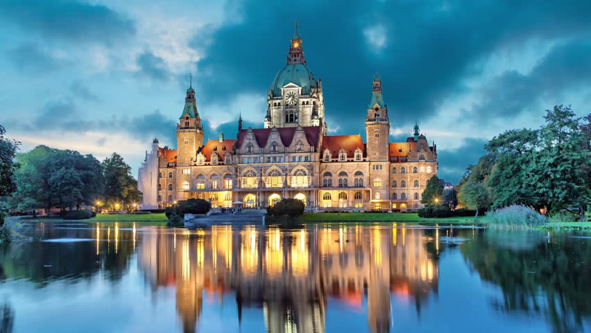 New City Hall of Hannover reflecting in water in the evening  (static image with animated sky)
