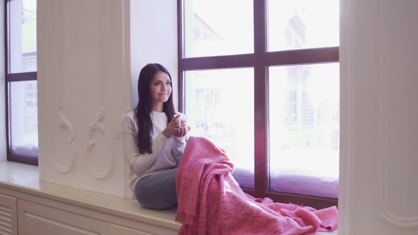 Smiling latin or indonesian girl 20-24 year old holding cup of tea or coffee sitting on windowsill and looking at window sunshine, slow motion. Morning relax