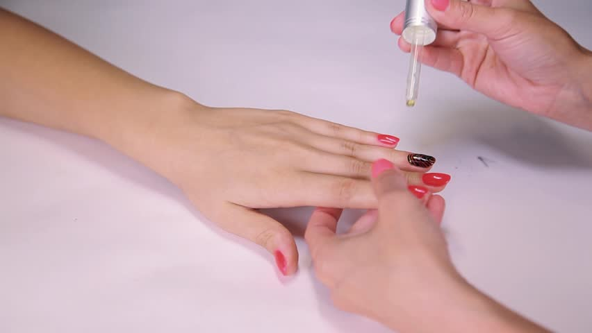 Woman beautician dropper put medicine on bright red nails polish in beauty saloon, close up | Shutterstock HD Video #23560069