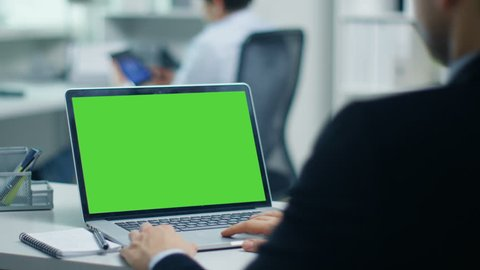Businessman Working on a Laptop with Green Screen on. In the Background His Colleague Working on a Tablet Computer. Office is Modern and Bright. Shot on RED Cinema Camera 4K (UHD).