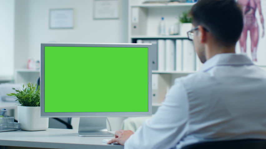 Doctor's Office. Male Doctor Works at His Personal Computer with Green Screen, His Assistant Comes in and Takes His Place at the Table. Modern Office. Shot on RED Cinema Camera 4K (UHD). | Shutterstock HD Video #23570899