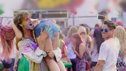 Excited boyfriend spanking girlfriend at Color festival, young people having fun