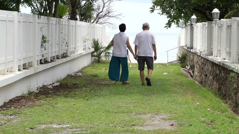 Older Asian senior couple walking to the beach white embracing each other through their vacation home