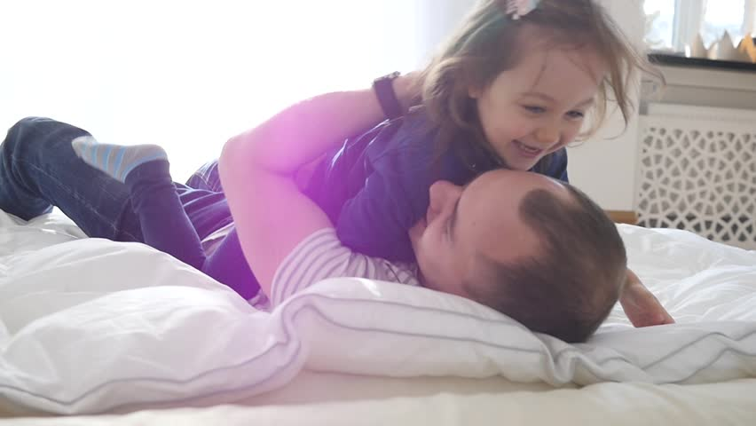 Happy Family Idyll Father Hug Little Child Daughter Playfully Roll Over A Bed At Home