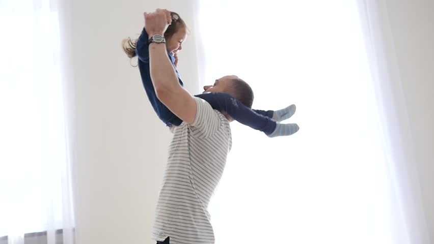 Happy Family At Home Father Entertain Little Child Daughter Throw Her In Air And Then They Falling On A Bed