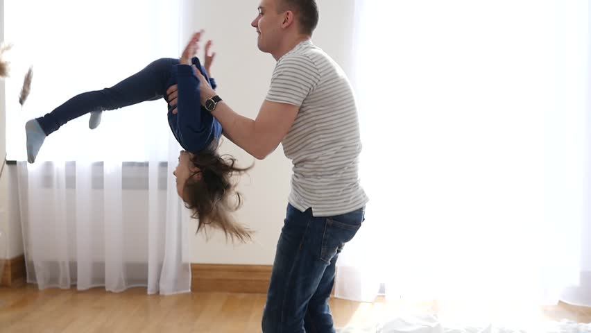 Happy Family At Home Father Entertain Little Child Daughter Throw And Spin Her In Air And Then They Falling On A Bed