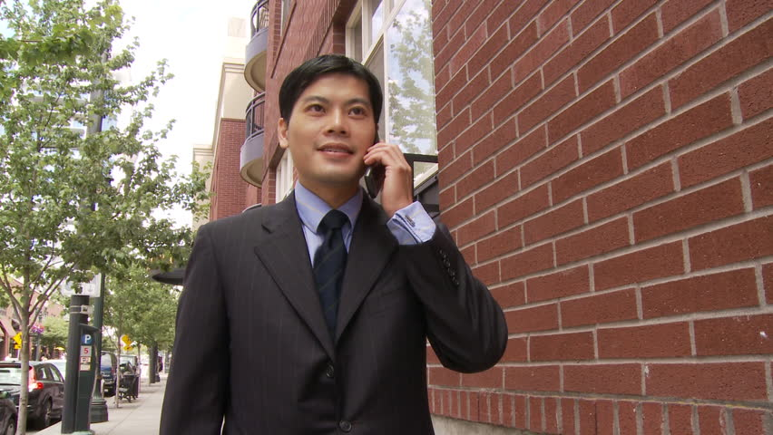 View of Man talking on Cell Phone while walking in USA
