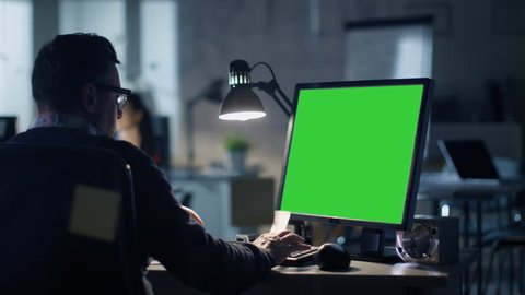 Late at Night Industrial Engineer Sits at His Desk Working on a Computer with Green Screen on. Office is Modern. In the Background Colleagues are Working at Their Desks. Shot on RED Cinema Camera 4K