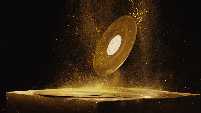 Vintage golden vinyls with golden dust falling down in front of black background. Shot on RED HELIUM Cinema Camera in slow motion.