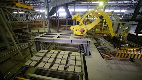 Industrial robotic arm manufacturing bricks. Timelapse.
