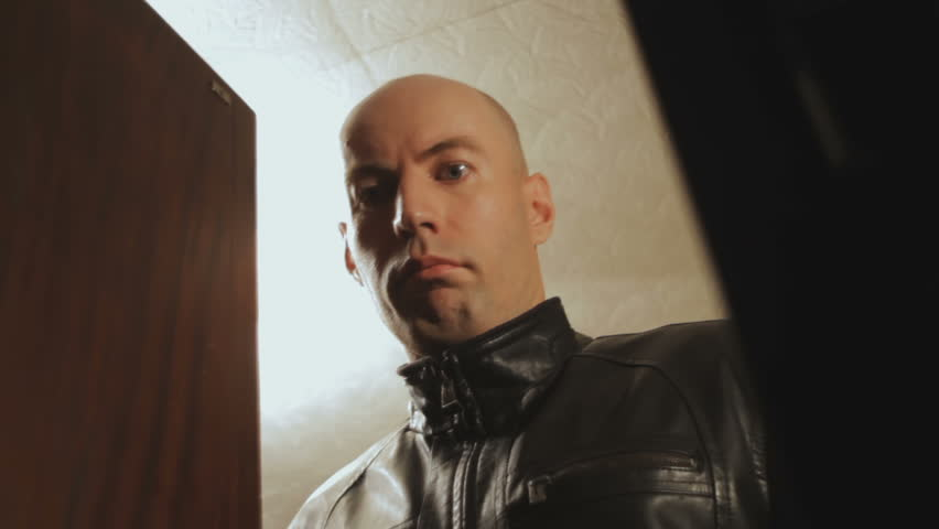 Bald guy is very surprised, opening the the closet door