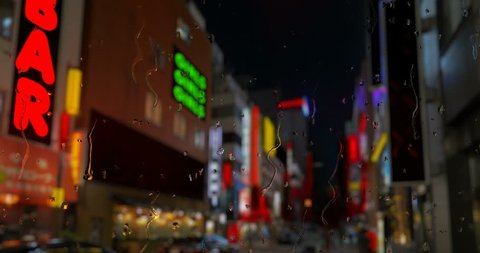 Red light district with strip bars and flashing signs with rain down a window in front. Mocked up image.