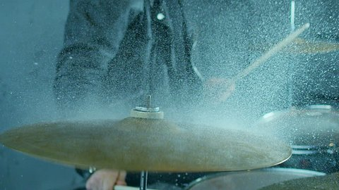 Drummer hitting on wet drum cymbal, and the water splashing from cymbal in slow motion 200 fps.  Shot on RED HELIUM Cinema Camera.