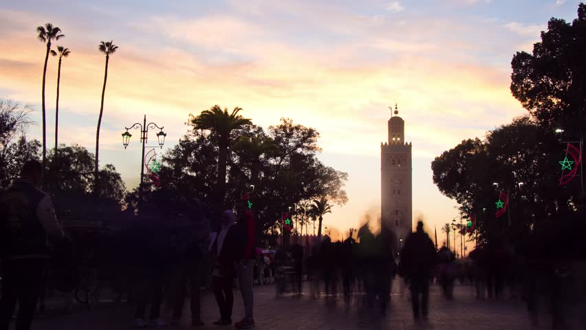Marrakech, Morocco - January 8, 2017: 4K Sunset timelapse over palm trees and the Koutoubia Mosque, with people walking around, next to Jemaa el Fna square.