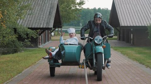 Biker with tie ride motorcycle with woman in nurse costume grimacing in sidecar
