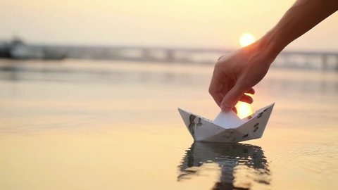 Man's hand launches paper boat on the water and pushing it away during beautiful sunset with reflection sun in the sea in slowmotion. 1920x1080