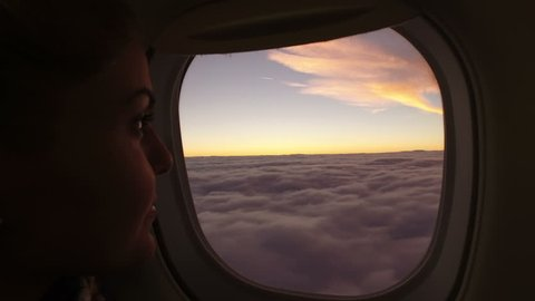 Girl looks at the clouds from airplane window in beautiful sunset scene