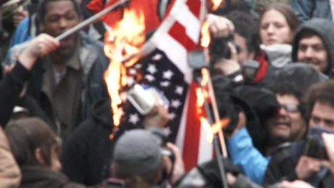 PORTLAND, OREGON - CIRCA 2017: Large group of angry people gather together to burn American flags in protest to Donald Trump taking office.