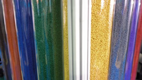 Samples of multi-colored plastic pellets in transparent containers. In the tubes are blue, white, green, red, yellow, pink, grey polymer granules. Shot in motion