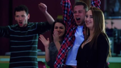 Friend emotions of playing bowling game HD slow-motion video. Young man and girls watches, haves fun, applauds and happy for win. Lucky shot hit. Hobby, leisure and competitions