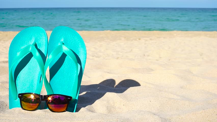 3600cf0c3522 Flipflops and Sunglasses on Sandy Ocean Beach. Closeup. Summer Vacation  Concept