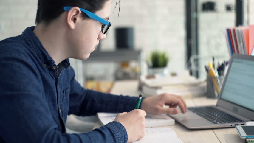 Young teenager doing homework with laptop by the desk at home  | Shutterstock HD Video #23897290