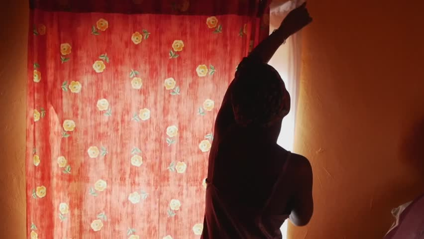 Rural black South African woman waking up and opening curtains in the morning | Shutterstock HD Video #23933869