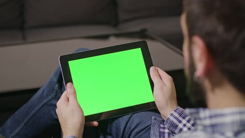 Young man using digital tablet pc with blue screen sitting at home. tap
