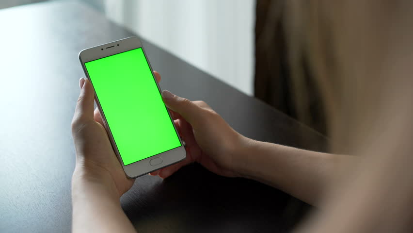 One person use cellular telephone with touch green screen for browsing social networks and communicating closeup. Girl, holding in hand portable gadget close up, as image of tech accessibility concept | Shutterstock HD Video #23974873