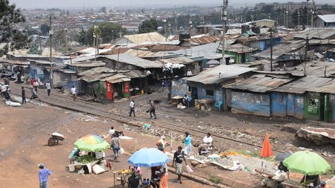 NAIROBI, KENYA, January 18th 2016: Residents of Kibera going about daily life with makeshift corrugated metal shacks and buildings and train line running through the slum