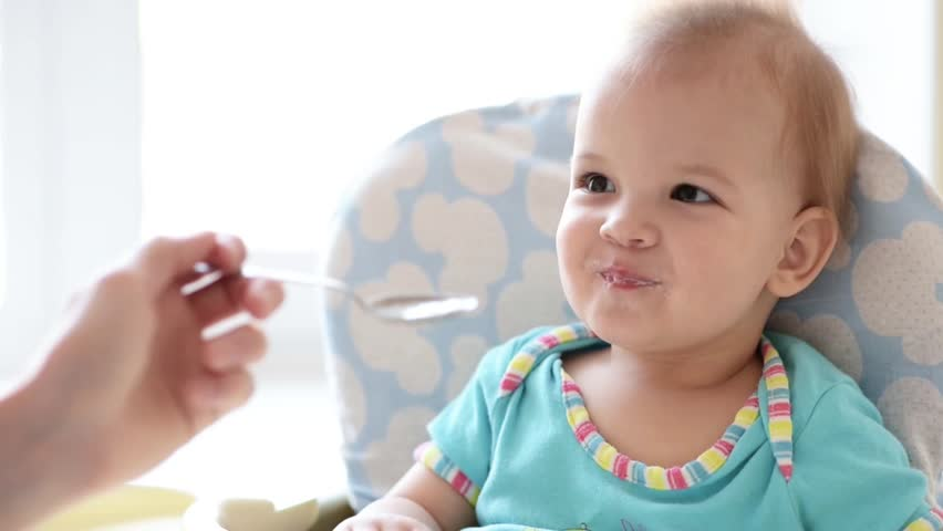 Mother gives baby food from a spoon