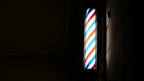 Barber pole spinning at night. International barbershop pole sign