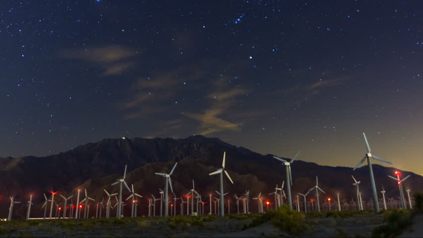 Astrophotography timelapse with tilt up motion of constellation Orion over windmills in Palm Springs, California