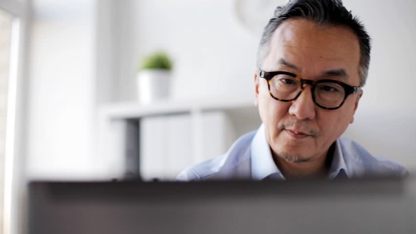 Business, people and technology concept - businessman in eyeglasses with laptop computer at office