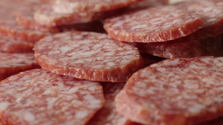 Food background of cured sausage of air-dried meat cuts 4K 2160p 30fps UltraHD  tilting footage - Salami  smaller pieces served on plate slow tilt 3840X2160 UHD video